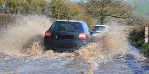 Car driving through a flooded road in East Devon