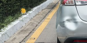 Backside of car has dented rear bumper damaged after accident on the road